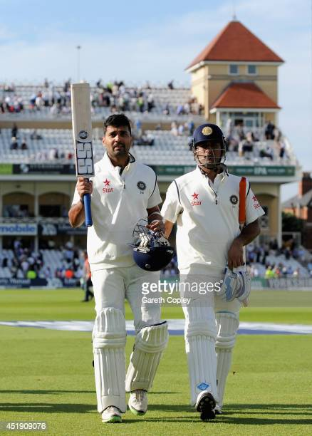 Murali Vijay of India raises his bat as he leaves the field alongside Mahendra Singh Dhoni of India at stumps on day one of 1st Investec Test match...