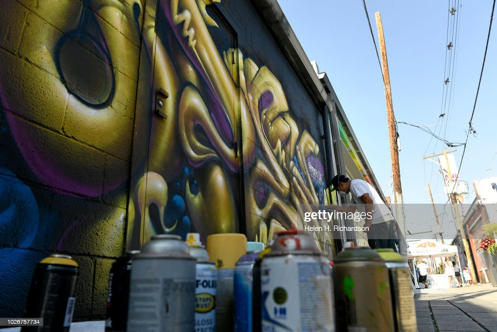 muralist and artist mpek works on his mural in alley one between