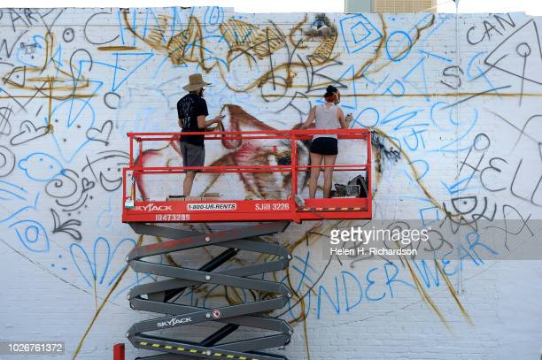 Muralist and artist Nicholas Napoletano right gets help from his sister Marissa as the two work on his mural on a large brick wall in a parking lot...