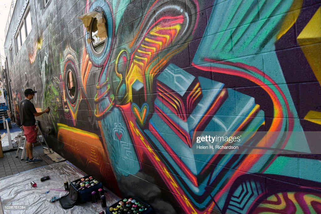 muralist and artist pharaoh one works on his mural in alley one