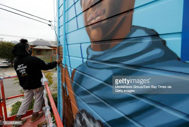 Muralist Rachel Wolfe Goldsmith paints a Black Panther Party mural on Jilchristina Vest's home at the corner of Center and 9th Streets in West...
