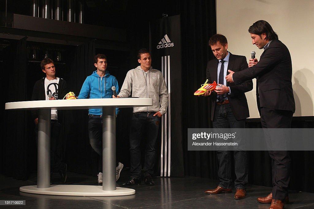 Murat Yakin (R), head coach of FC Luzern talks whilst Swiss Swiss national football players Valentin Stocker (L), Admir Mehmedi (2nd L) and David Dehen (C) looks on during the adidas adizero F50 miCoach launch event at Miller studio on November 7, 2011 in Zurich, Switzerland.