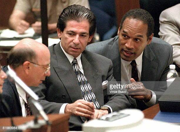 Murder defendant OJ Simpson consults with friend Robert Kardashian and Alvin Michelson the attorney representing Kardashian during a hearing about...
