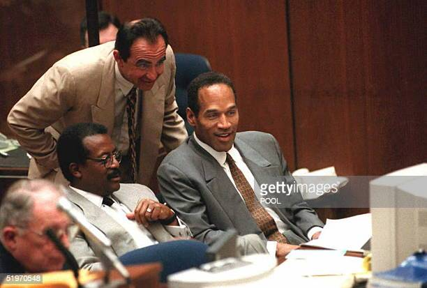 Murder defendant O.J. Simpson smiles with his attorneys Robert Shapiro and Johnnie Cochran Jr as they view a video tape 06 February showing Simpson...