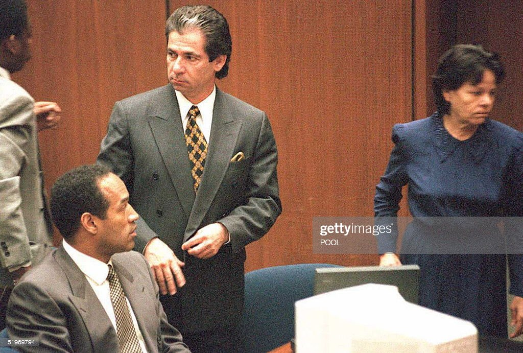 Murder defendant O.J. Simpson(L, sitting) watches defense witness Rosa Lopez enter the court for a hearing on how her testimony will be heard 27 February. Superior Court Judge Lance Ito decided that Lopez's testimony will be videotaped without a jury present. Standing next to Simpson is Robert Kardashian.
