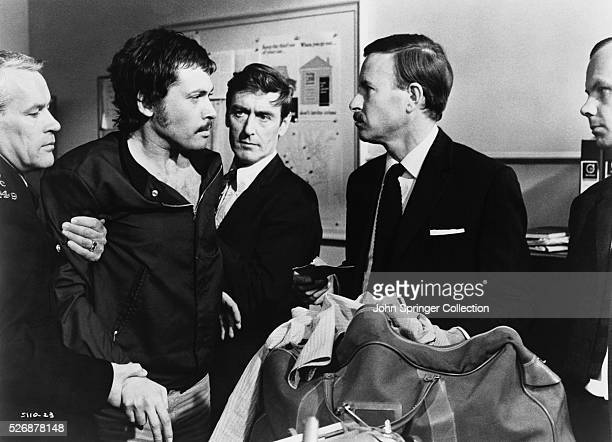 Murder suspect Richard Blaney is held by police officers while being confronted by Chief Inspector Oxford in Alfred Hitchcock's thriller Frenzy