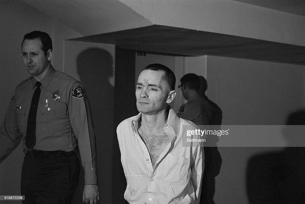 Murderer Charles Manson, clean-shaven and with a short haircut, is escorted through a Los Angeles courthouse by sheriff's deputies. A swastika marks his forehead.