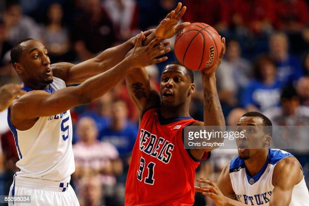 Murphy Holloway of The Ole Miss Rebels looks to pass the ball around Ramon Harris and Perry Stevenson of the Kentucky Wildcats during the first round...