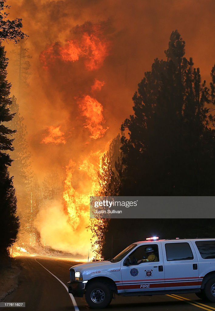 A Murphys Fire District firefighter stops his vehicle as a massive wall of fire from the Rim Fire consumes trees along highway 120 on August 24, 2013 near Groveland, California. The Rim Fire continues to burn out of control and threatens 4,500 homes outside of Yosemite National Park. Over 2,000 firefighters are battling the blaze that has entered a section of Yosemite National Park and is currently 5 percent contained.
