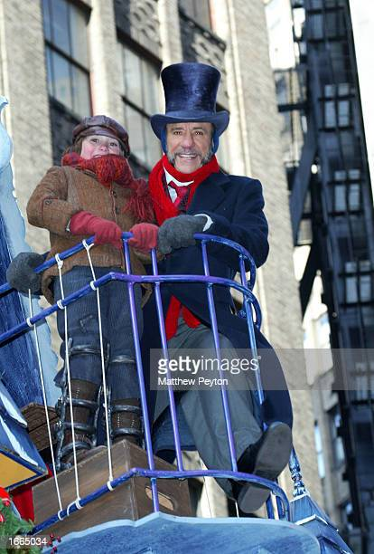 F Murray Abraham dressed as Charles Dicken's character Ebeneezer Scrooge and accompanied by an actor playing Tiny Tim from the novel A Christmas...
