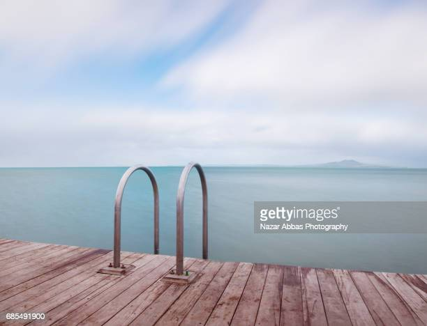 Murrays Bay Jetty With Background Of Rangitoto Island, Auckland, New Zealand.
