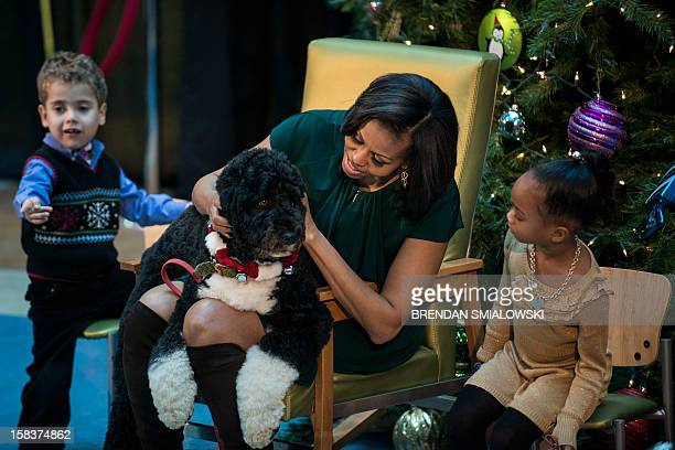 AJ Murry and Jordyn Akuoko watch as US first lady Michelle Obama covers the first family's dog Bo while talking about his holiday gifts at Children's...