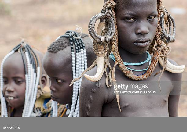 Mursi tribe children with adornments on the heads omo valley mago park Ethiopia on March 18 2016 in Mago Park Ethiopia