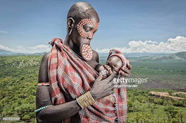 Mursi woman with a lip plate holding her child on a lookout of the Omo valley