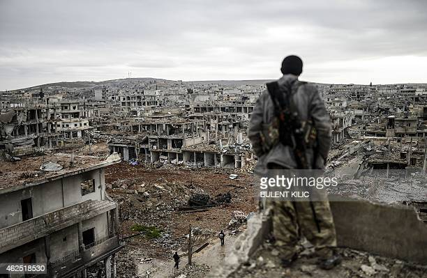 Musa a 25yearold Kurdish marksman stands atop a building as he looks at the destroyed Syrian town of Kobane also known as Ain alArab on January 30...