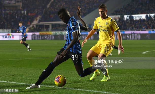 Musa Barrow of Atalanta BC competes for the ball with Valerio Verre of Hellas Verona during the Serie A match between Atalanta BC and Hellas Verona...