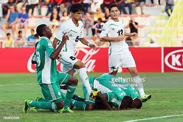 Musa Muhammed of Nigeria celebrates his team's first goal with team mates during the FIFA U17 World Cup UAE 2013 Group F match between Nigeria and...