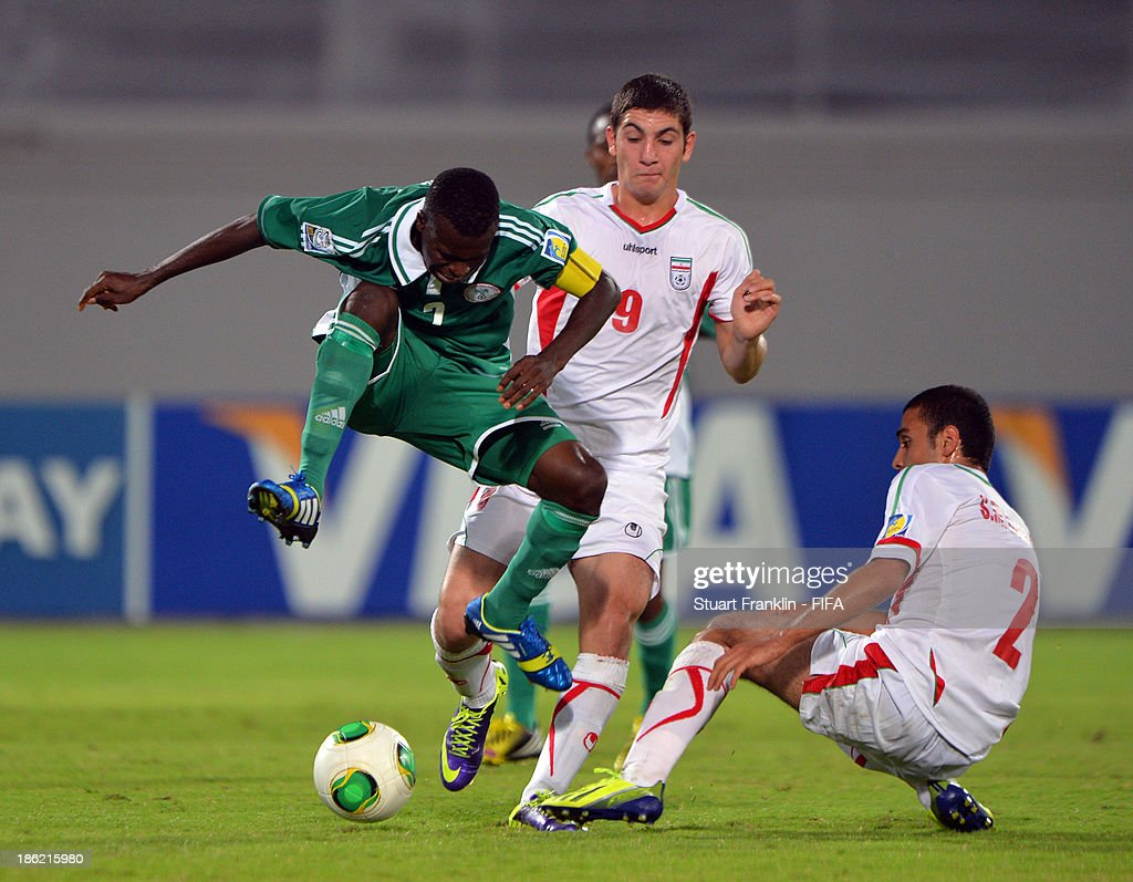 Musa Muhammed of Nigeria is challenged by Mostafa Hashemi of Iran during the round of 16 match between Nigeria and Iran at Khalifa Bin Zayed Stadium on October 29, 2013 in Al Ain, United Arab Emirates.