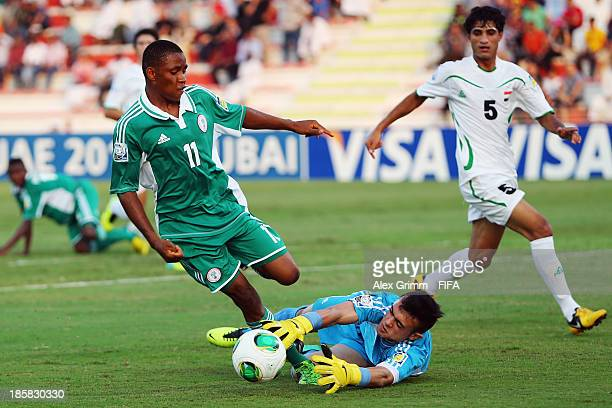Musa Yahaya of Nigeria is challenged by goalkeeper Hayder Mohammed of Iraq during the FIFA U17 World Cup UAE 2013 Group F match between Nigeria and...