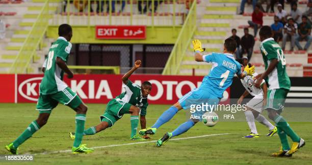 Musa Yahaya of Nigeria scores his team's fourth goal against goalkeeper Hayder Mohammed of Iraq during the FIFA U17 World Cup UAE 2013 Group F match...