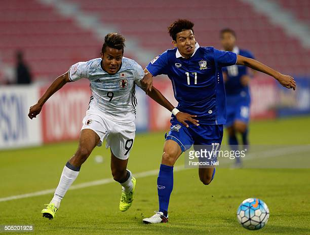 Musashi Suzuki of Japan battles for the ball with Tanaboon Keserat of Thailand during the AFC U23 Championship Group B match between Thailand and...