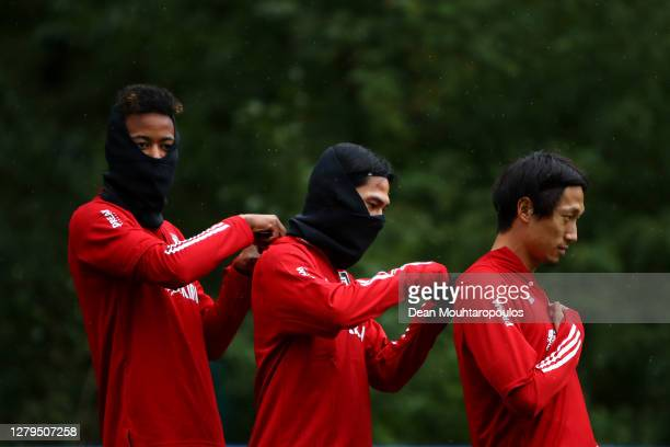 Musashi Suzuki, Takumi Minamino and Sei Muroya of Japan adjust each others electronic tracking devices during a Japan training session at Soccer Club...