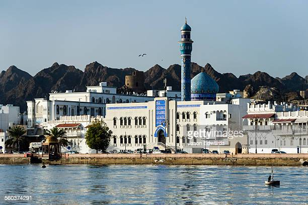 Desert mountains tower over whitewashed walls of a mosque and minaret behind a shopping and hotel district on the shores of the Gulf of Oman.