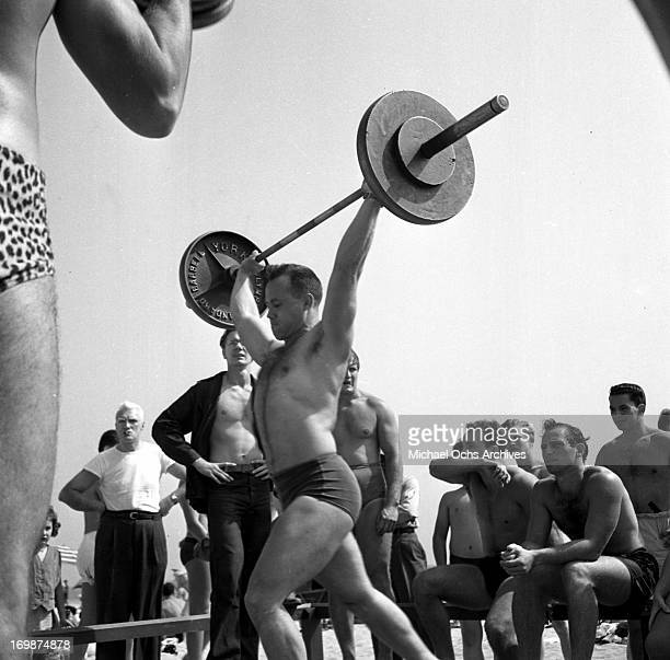 A muscle builder lifts weights at Muscle Beach on July 24 1949 in Santa Monica California