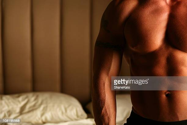 muscle man on bed - naturists stock pictures, royalty-free photos & images