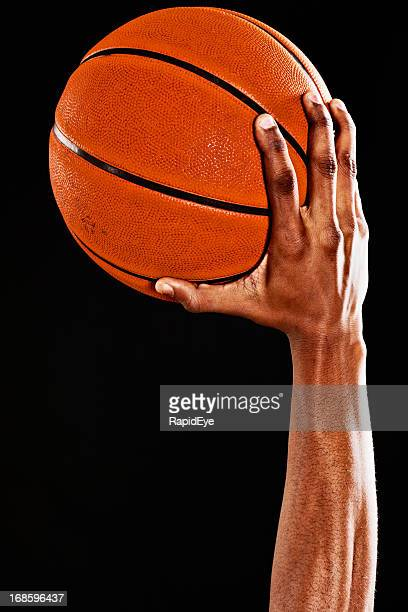 Muscular arm of a basketball player ready to shoot