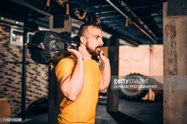 muscular athlete doing core bag squats workout in a gym gym - sandbag stock pictures, royalty-free photos & images