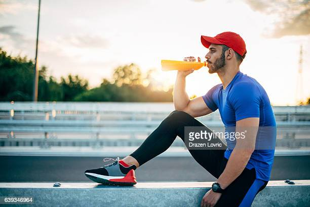 Muscular athlete resting and drinking energy drink