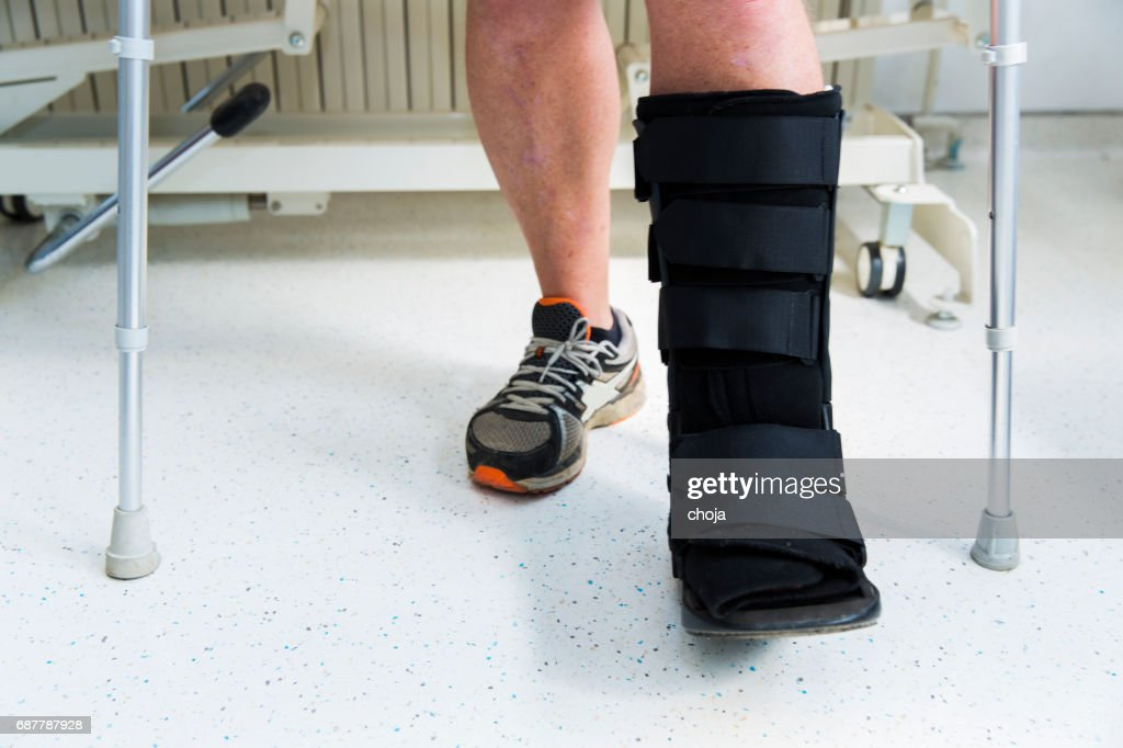 Muscular athlete with Walking boot for achilles tendon treatment : Stock Photo