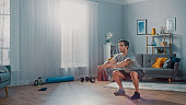 Muscular Athletic Fit Man in T-shirt and Shorts is Doing Squat Exercises at Home in His Spacious and Bright Living Room with Minimalistic Interior.