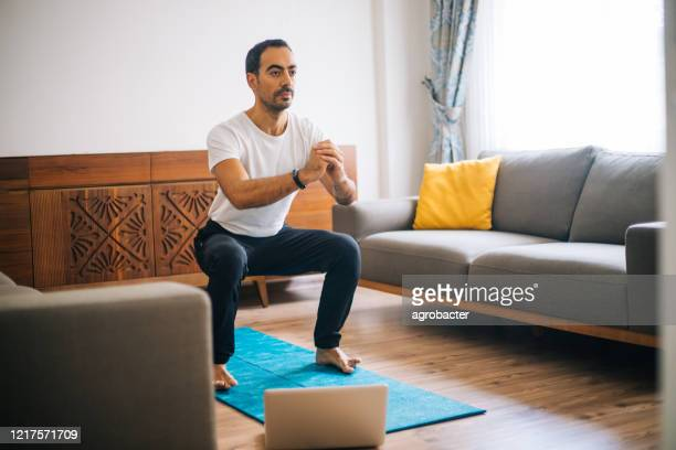 muscular athletic fit man in t-shirt and shorts is doing squat exercises at home - crouching stock pictures, royalty-free photos & images