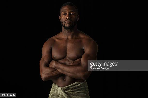 Muscular Black man bare chest arms crossed towel