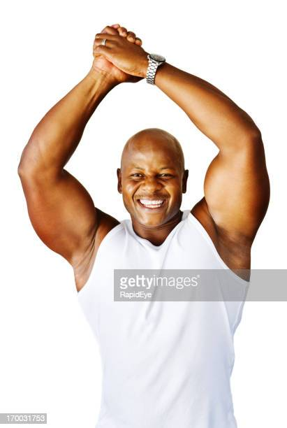 Muscular body builder smiles and raises clasped hands in triumph