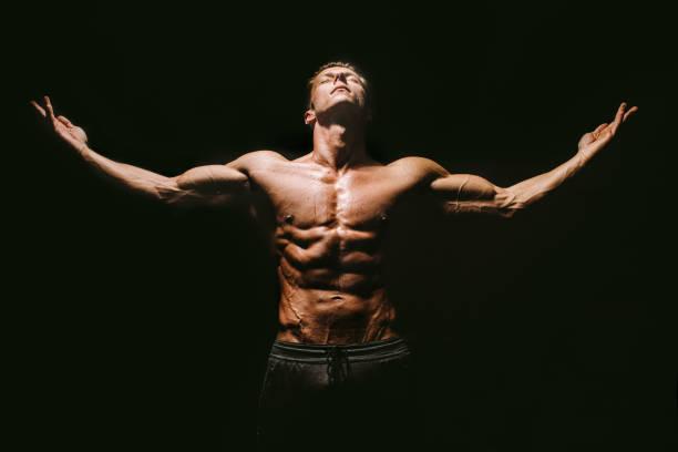 Muscular body man posing on black background
