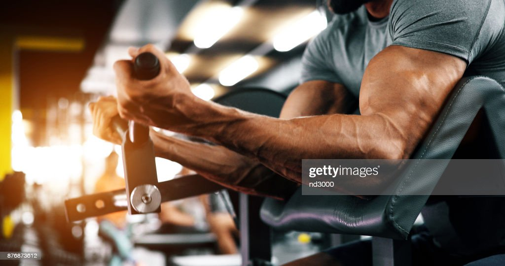 Muscular bodybuilder guy doing exercises : Stock Photo