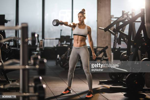 muscular build athlete having weight training with kettle bell in a health club. - homens musculosos imagens e fotografias de stock