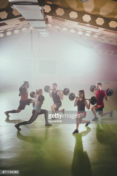 muscular build athletes exercising with barbell in a lunge. - circuit training stock photos and pictures