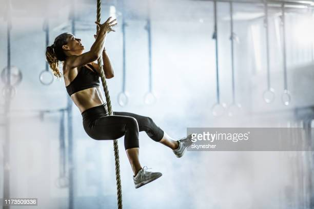 muscular build athletic woman moving up the rope in a gym. - female bodybuilder stock pictures, royalty-free photos & images