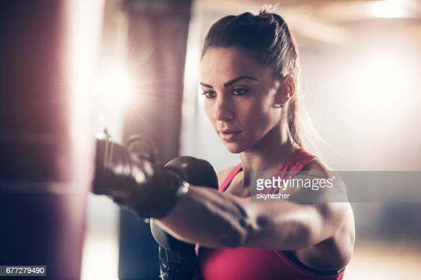 Muscular build female boxer having sports training in a gym.