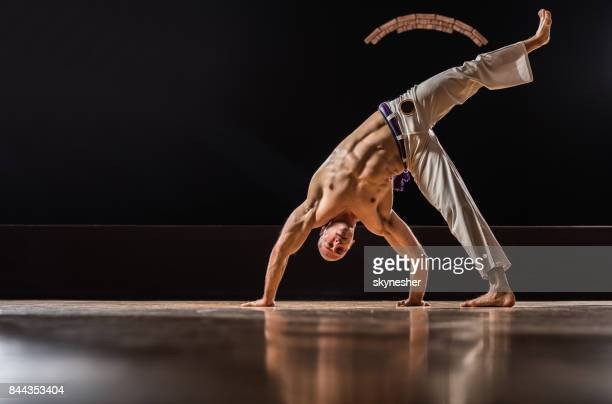 Muscular build man exercising capoeira in a health club.