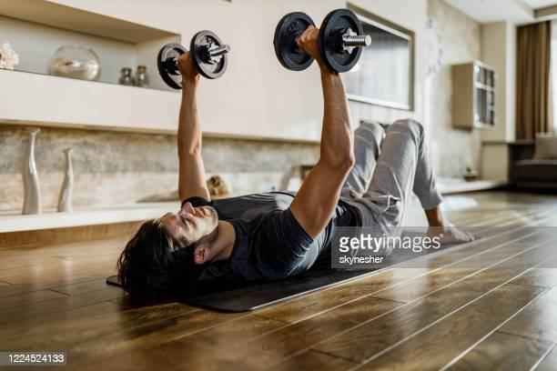 muscular build man exercising strength with weights on a floor. - weights stock pictures, royalty-free photos & images
