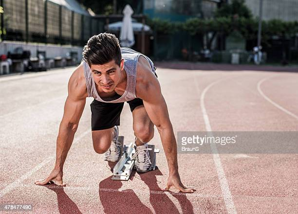 Muskulös Mann in der Startlinie auf Sportereignisse verfolgen.