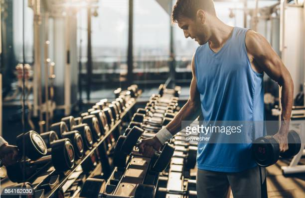 muscular build sportsman taking weights from a rack in a gym. - hand weight stock pictures, royalty-free photos & images