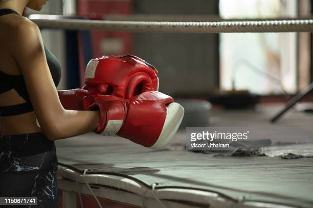 Muscular build woman getting ready for boxing exercise at fitness studio.