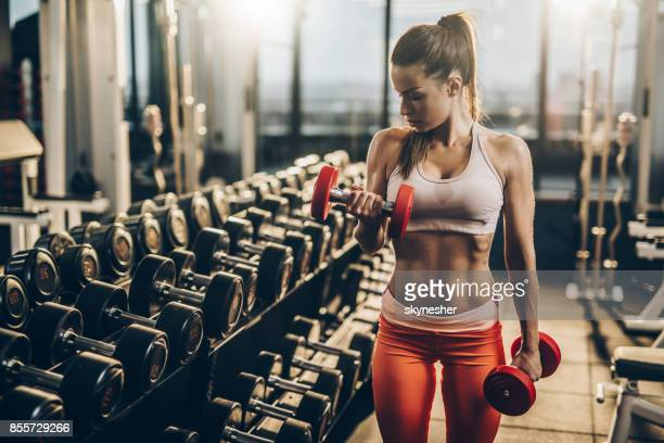muscular build woman having a weight training in a gym. - body building stock photos and pictures