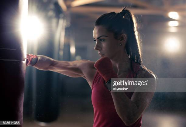 Muscular build woman punching a bag on a boxing training in a health club.